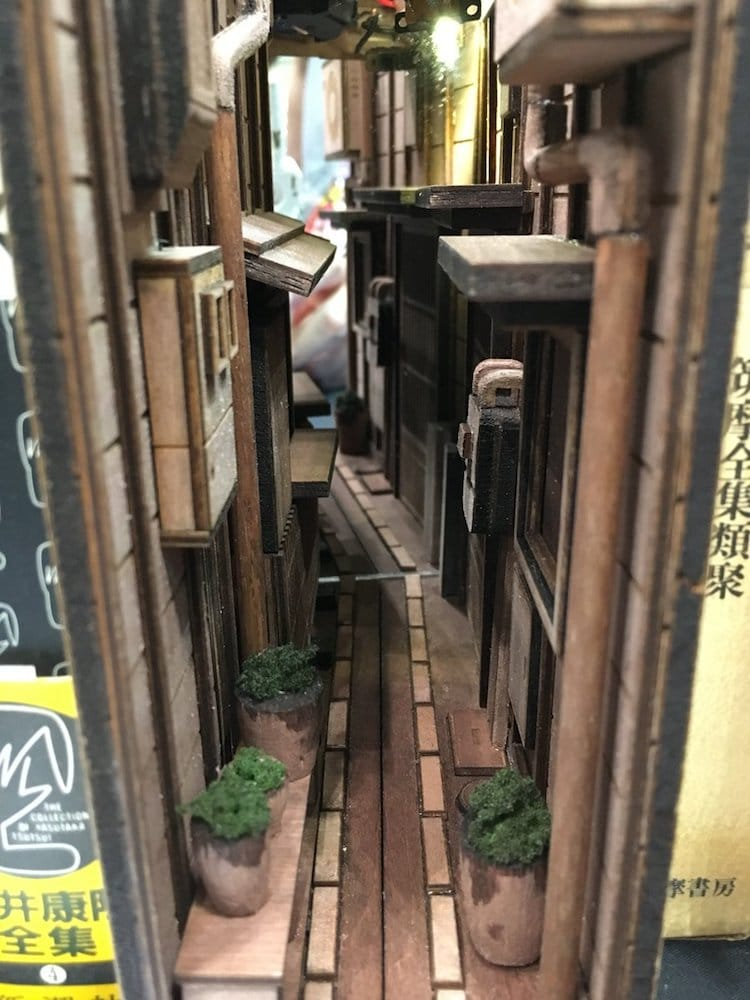 "Diorama of Tokyo's back alleyways, sized for a bookshelf. Sculpted by monde."" alt=""We peer into a narrow alleyway, flanked on both sides by buildings -- windows, potted plants, and balconies. It is no real alleyway, but a diorama that's designed to fit on a bookshelf next to other books."